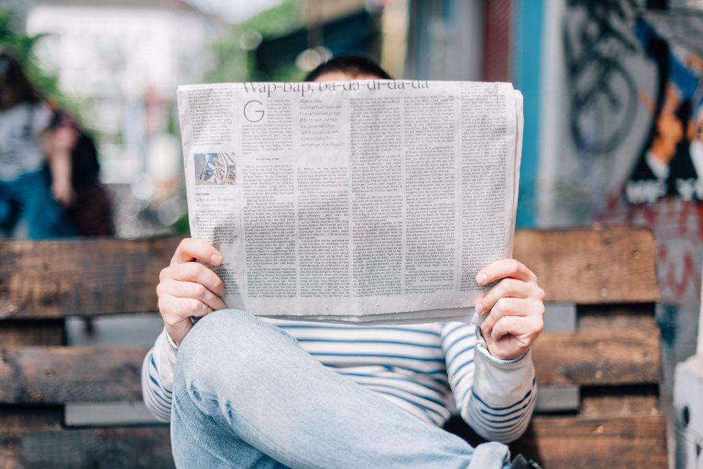 Uomo che legge le notizie al giornale