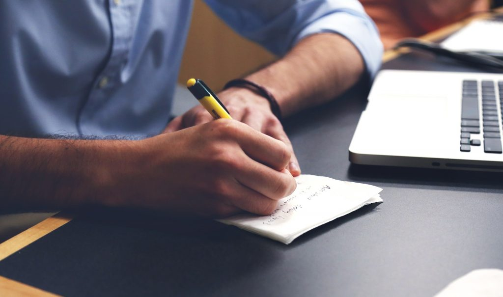 Immagine con uomo che scrive con metodo della piramide inversa
