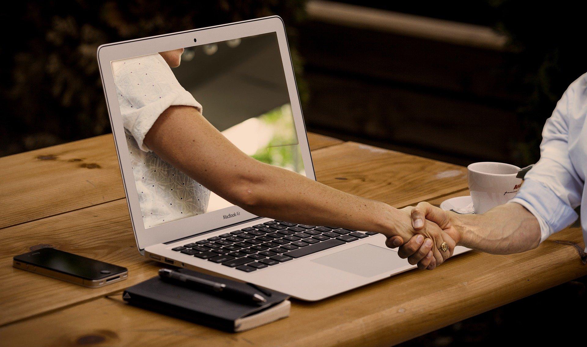 Il fattore umano: un pc, una mano che esce dallo schermo e ne stringe un'altra